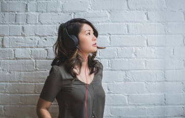 Woman in grey listening to music with headphones