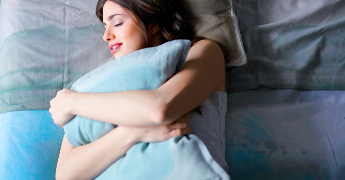 A woman hugging a pillow in bed